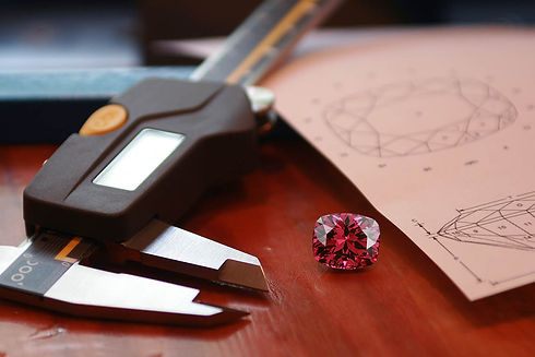 Faceted spinel, resting beside gem calipers