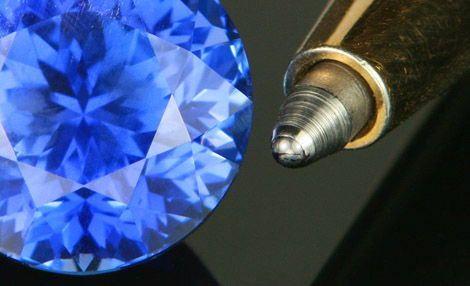 Precision cut sapphire, alongside a ball-point pen to illustrate the quality of Jeff White's gem cutting