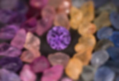 Fancy colors of sapphire, in both cut and rough forms.  Featured is a round brilliant purple sapphire cut by Jeff White