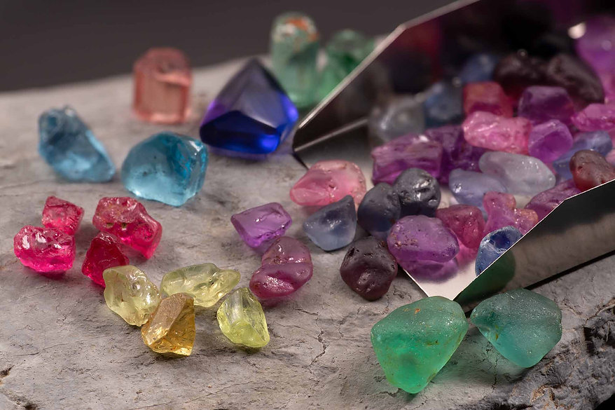 Assorted gem rough, spilling from a gem scoop.  Includes sapphire, tanzanite, aquamarine, spinel, tourmaline, and chrysoberyl