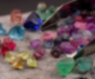 Assorted gemstone rough, spilling out of a gem scoop