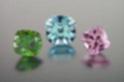 Custom cut chrome sphene, aquamarine, and pink topaz gemstones