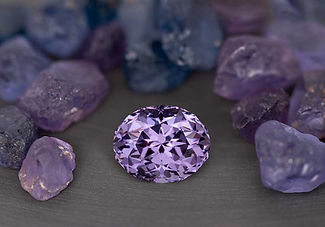 Custom cut lavender spinel, alongside rough lavender and blue spinels
