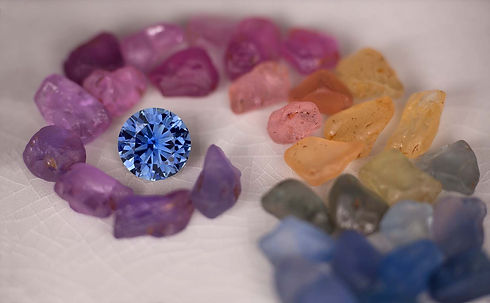 A rainbow of fancy sapphire colors, with a round brilliant blue sapphire at the center