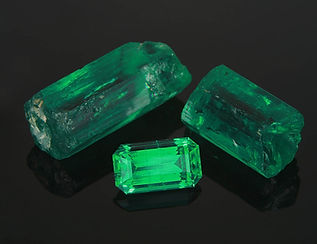 Unoiled, untreated custom cut emerald, along with rough