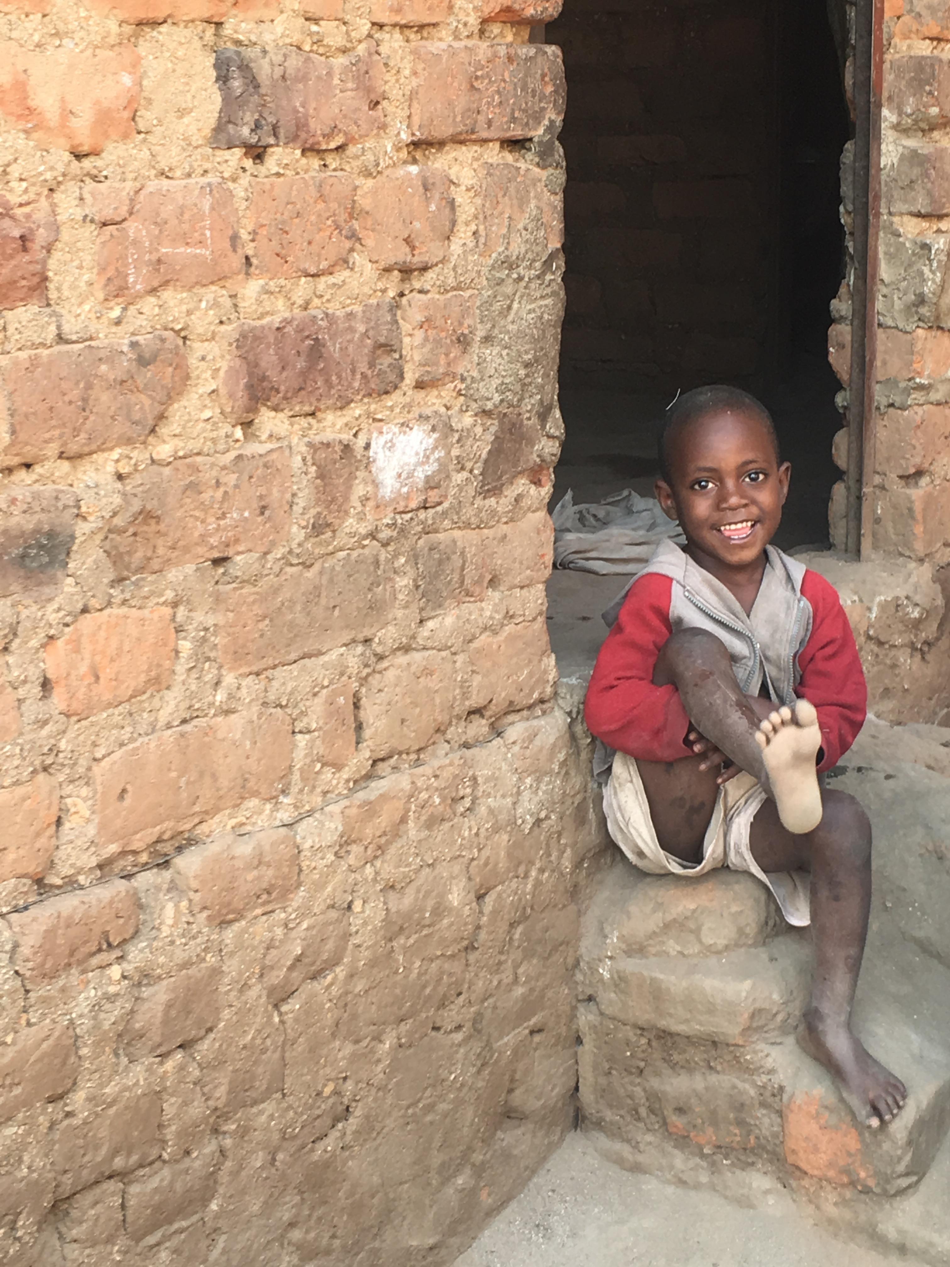 Ugandan child smiling at his home