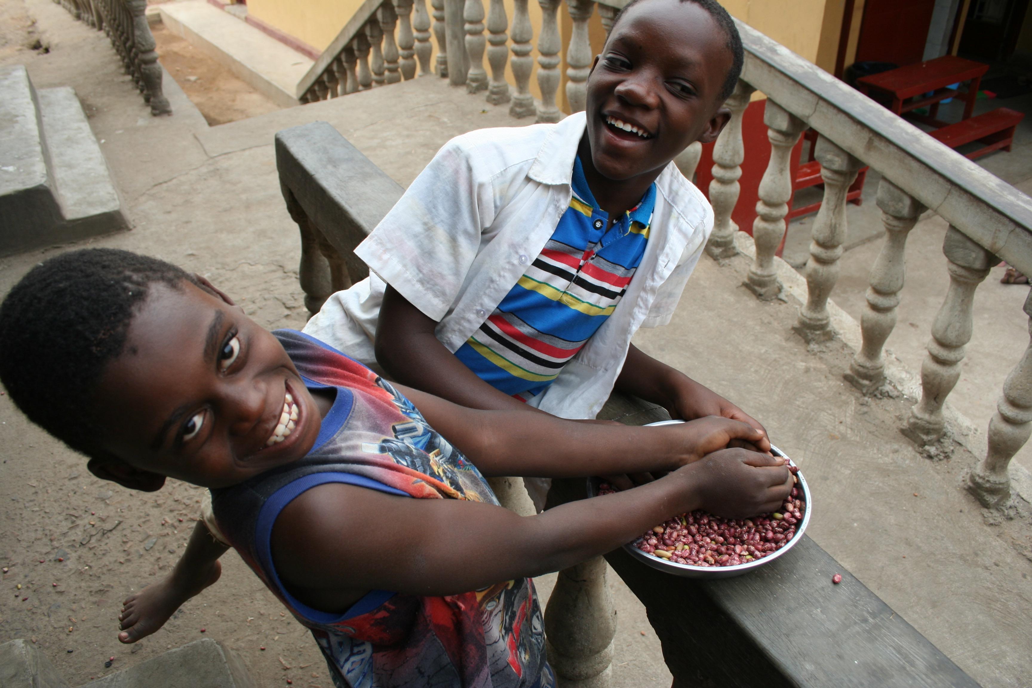 2 Ugandan boys smiling with food