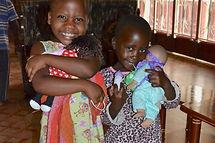Ugandan girls smiling with new dolls