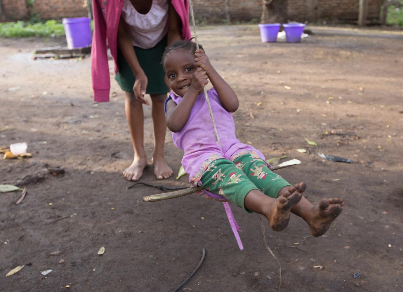 Ugandan child smiling and swinging