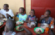 Ugana children eating at a table