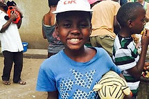 Ugandan boy smiling with new hat and toy
