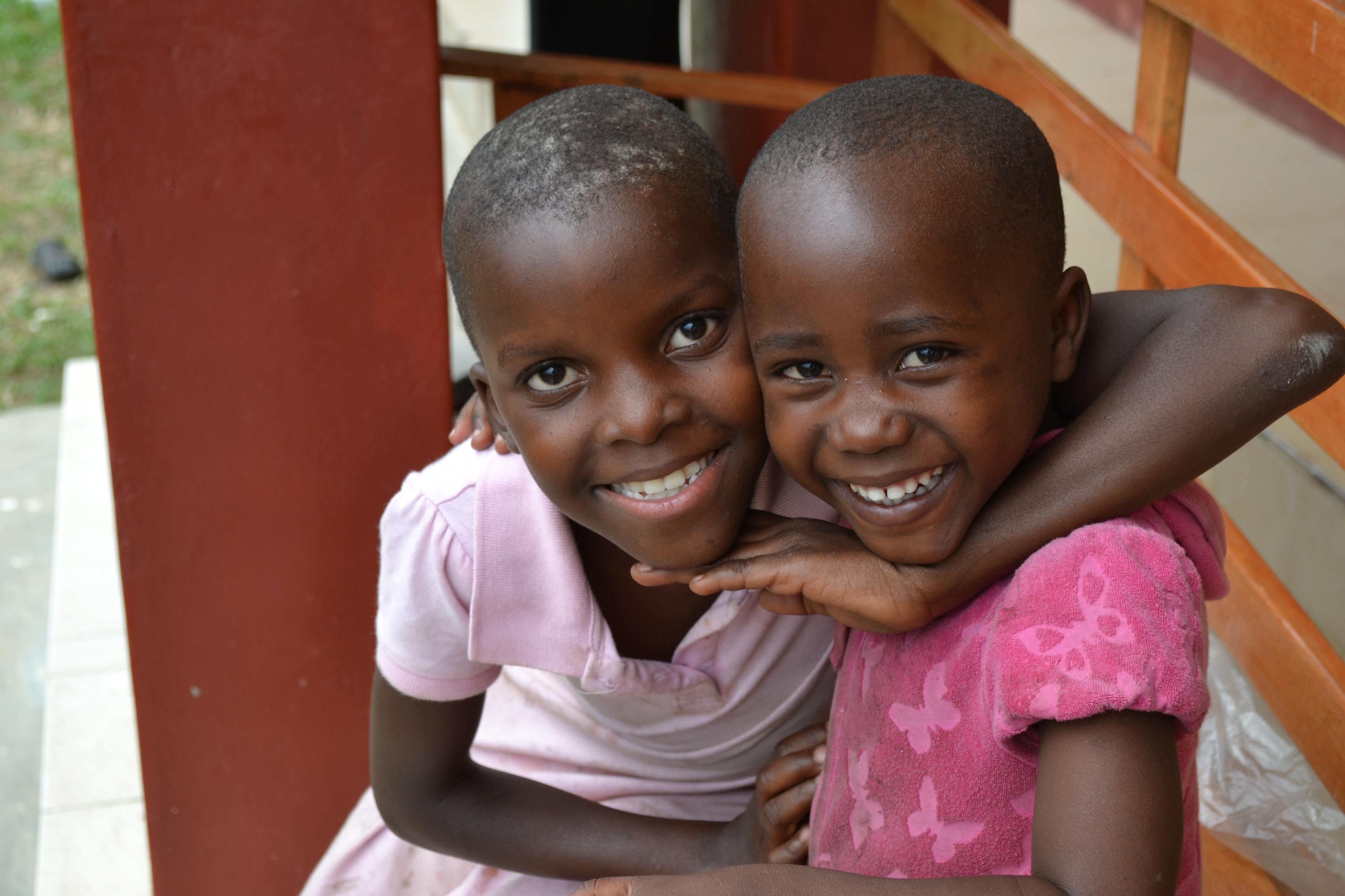2 Ugandan girls hugging and smiling
