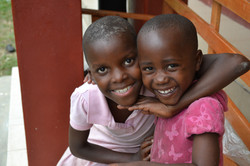 2 Ugandan girls hugging and smiling