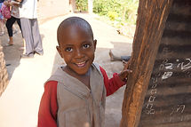 Ugandan child smiling in front of his home