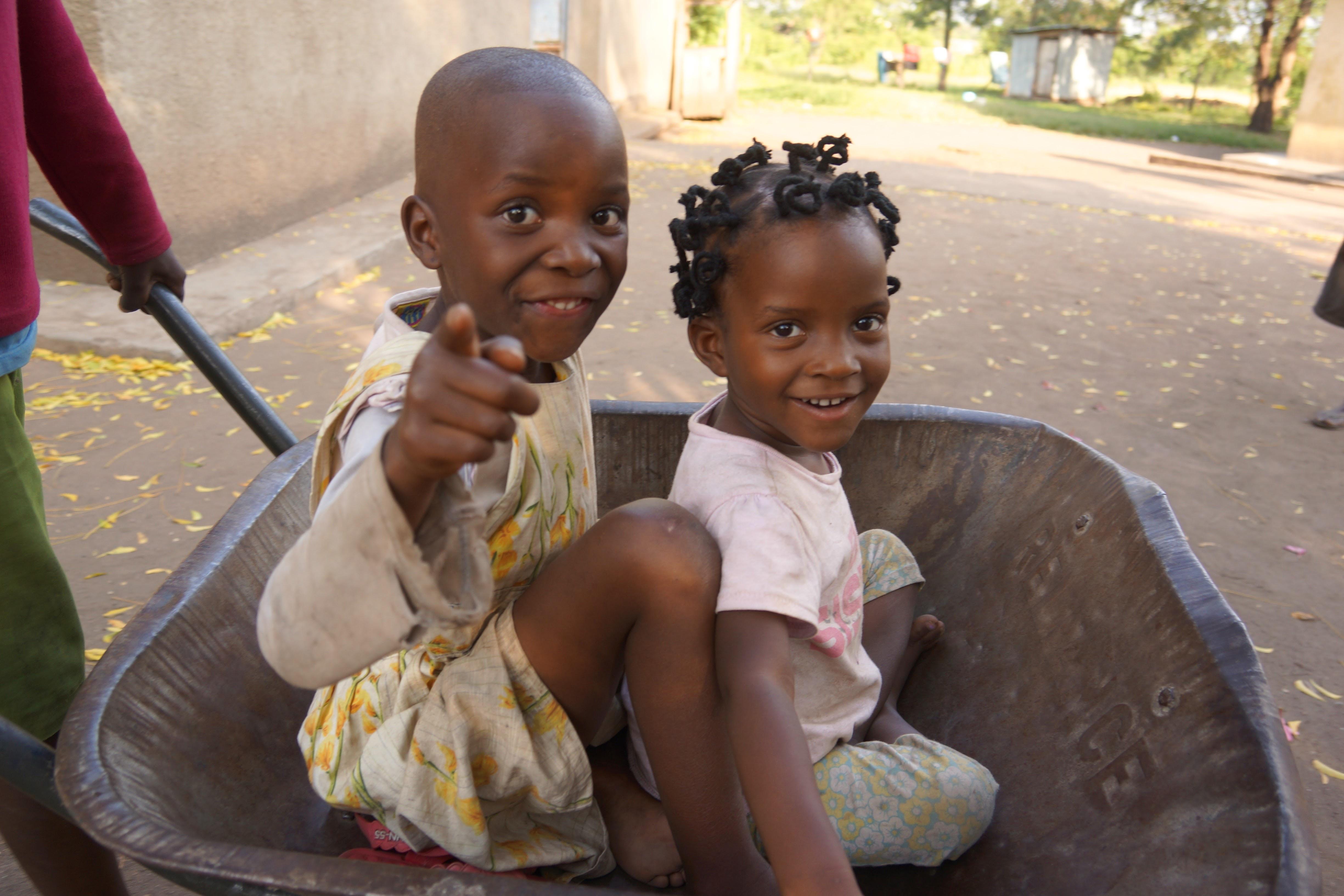 2 Ugandan girls in wheelbarrow