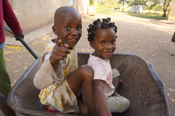 2 Ugandan girls in wheelbarrow