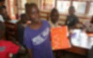 Ugandan boy holding a folder he decorated