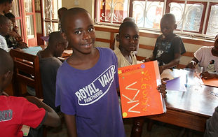 Ugandan boy holding a folder he decorated