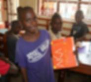 Ugandan child with folder he decorated