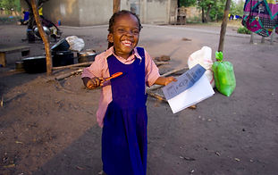Ugandan girl holding a book and pens on her first day of school