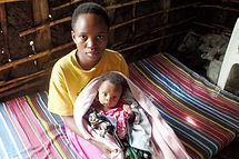 Ugandan children sitting on a mattress