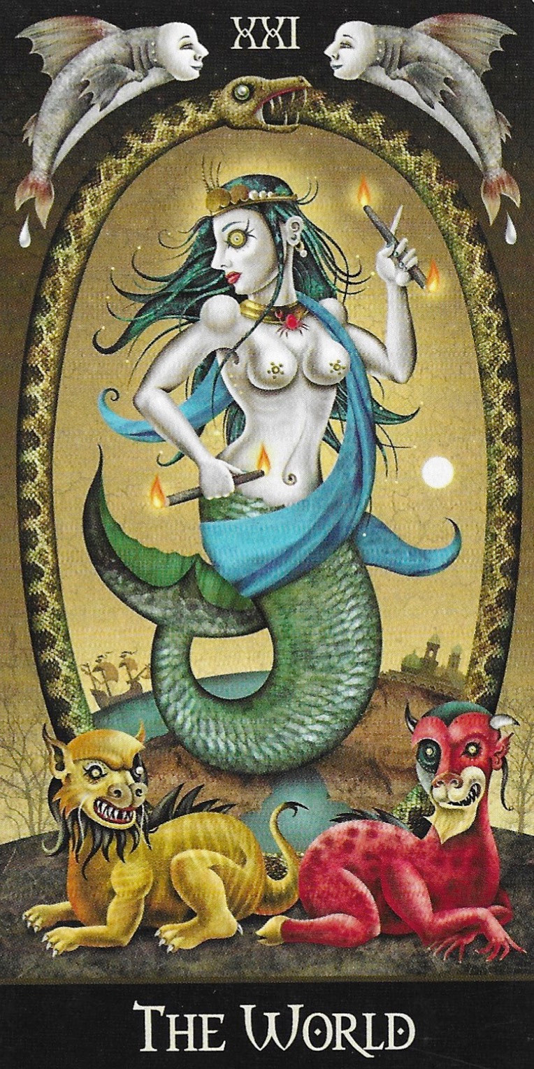 An ouroboros surrounds a mermaid in The Deviant Moon's World Card. With two flying fish overhead and a lion and beast at the mermaids feet. She holds to wands, each burning on both ends.