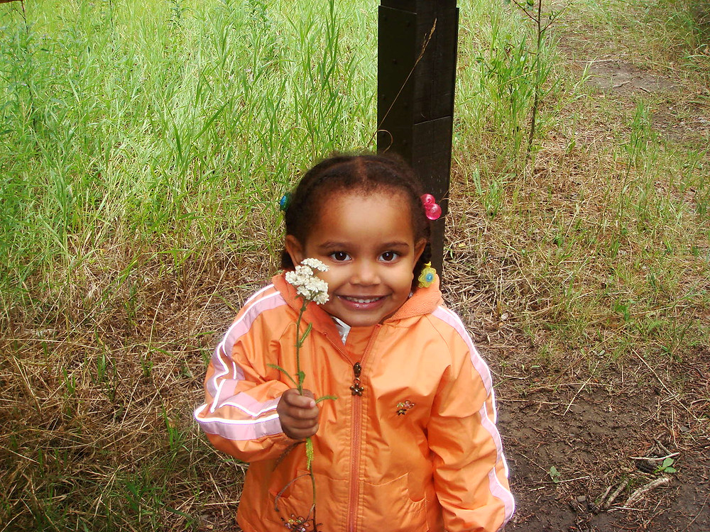 The miniStarlite when she was about 4 years old holding daisies