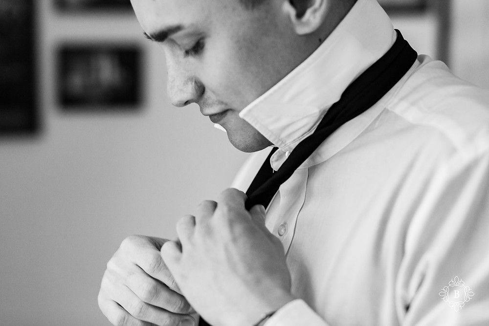 Rust Manor House groom prep tying tie black and white