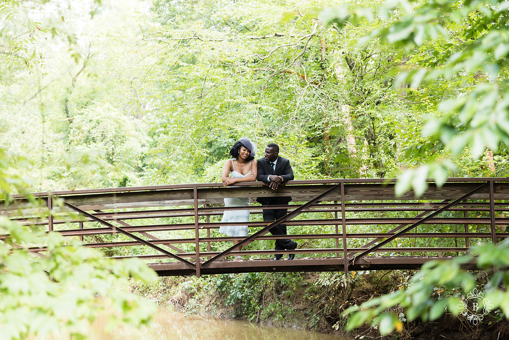 Candid photo of engaged couple on the Creek Trail bridge in Ellanor C. Lawrence park.