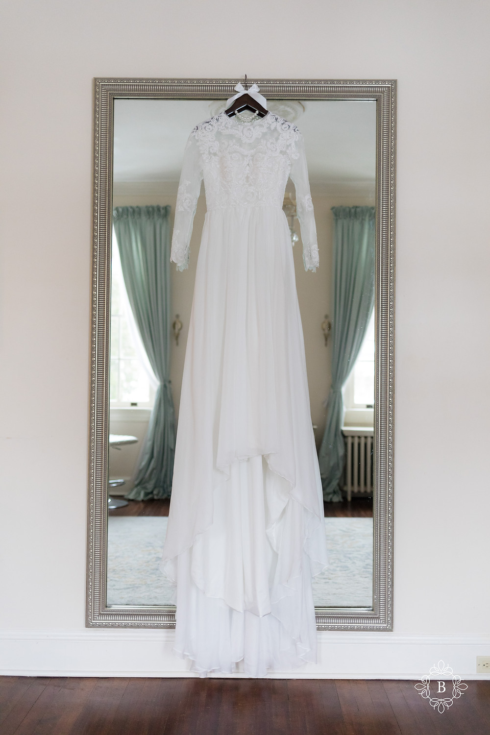 Rust Manor House elegant wedding dress hanging from mirror in bridal suite.