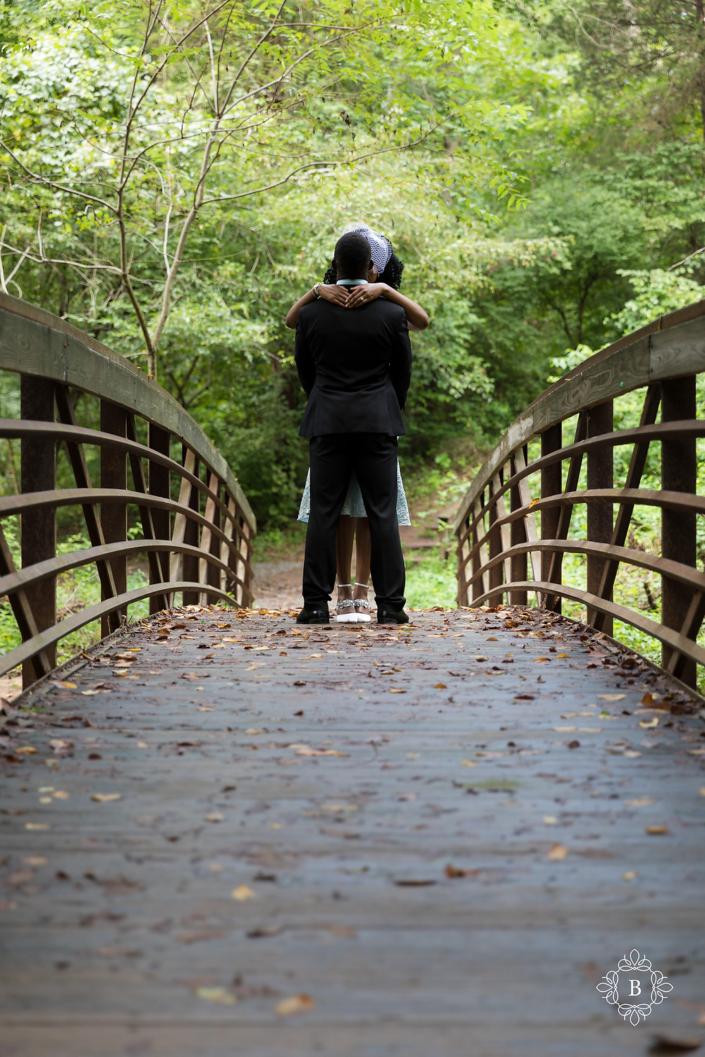 Engaged couple on the Creek Trail bridge in Ellanor C. Lawrence park.