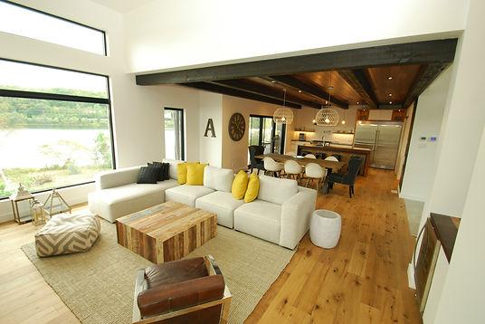 salon et cuisine ouverte blanche et plancher de bois