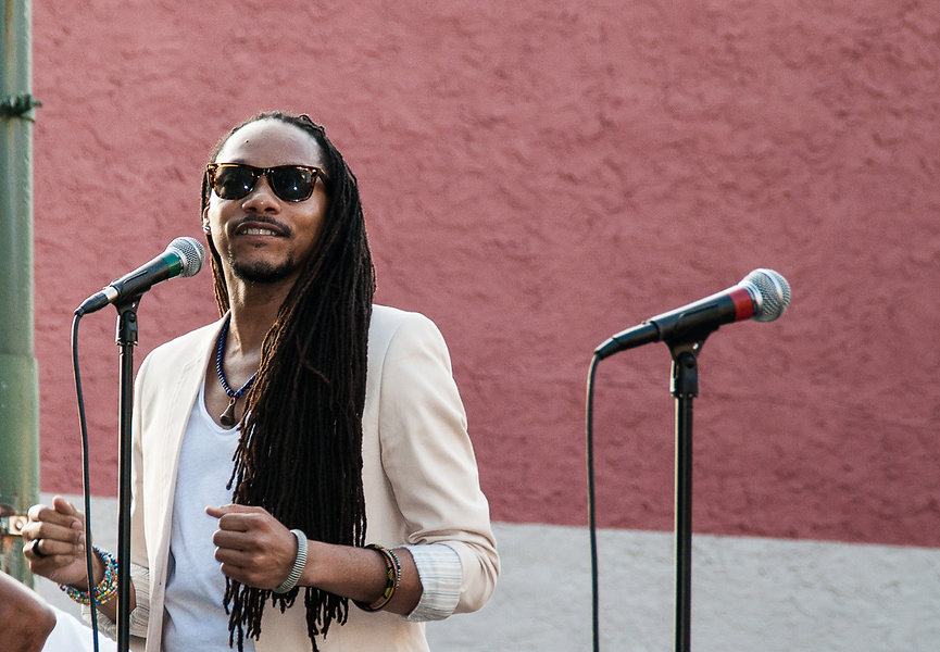 Man with dreadlocks and sunglasses sings at a microphone