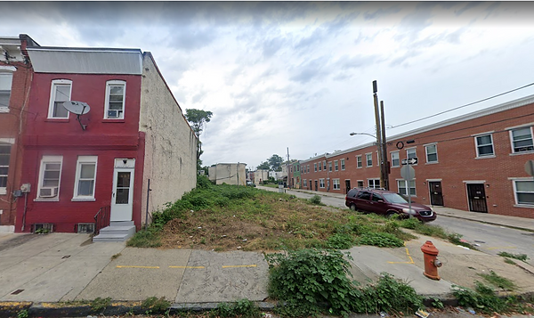 An empty lot on the corner of a block of row homes