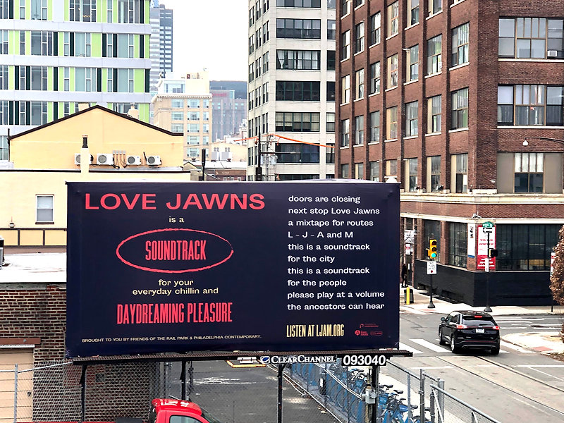 A billboard featuring a poem and advertising Love Jawns podcast surrounded by a cityscape