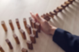 Businesswoman hand stopping the domino wooden effect concept for business.jpg