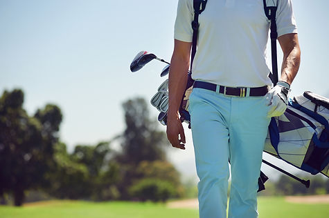 Golfer on the course with his golf bag