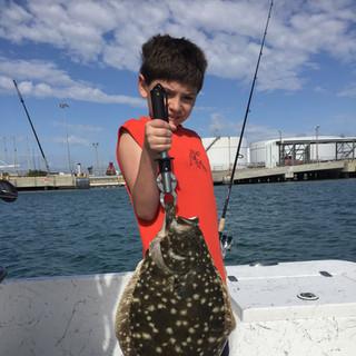kid holding fish he caught