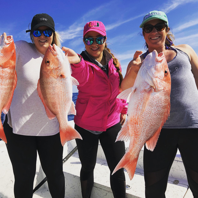 3 women holding 3 fish that they caught