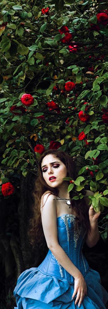 splendido ritratto di ragazza in abito d'epoca sartoriale tra fiori rossi