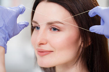 Cosmetologist plucks client eyebrows by