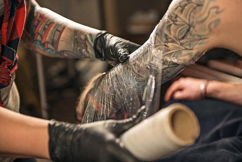 tattoo-artist-wrapping-client-s-arm-in-p