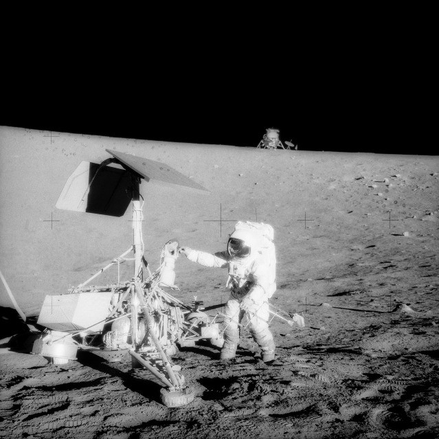 The Apollo 12 Lunar Module (LM) is in the background. The unmanned Surveyor 3 spacecraft is in the foreground. Credit: NASA