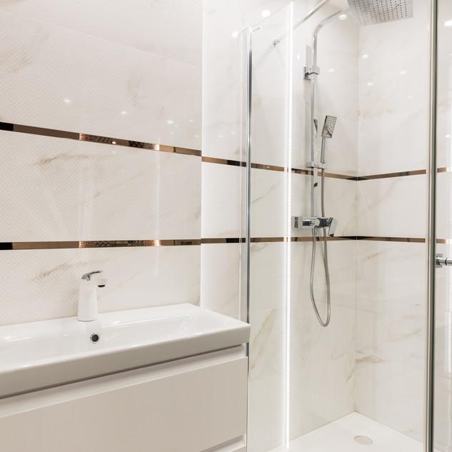 Ekspozycja łazienki w sklepie Staltex w Nadarzynie. Szafka z umywalką i prysznic.
