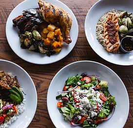 Assortment of Bushfire Kitchen items including Greek Salad, Chicken and Rib Combo, Salmon Bowl, and Carnitas Bowl