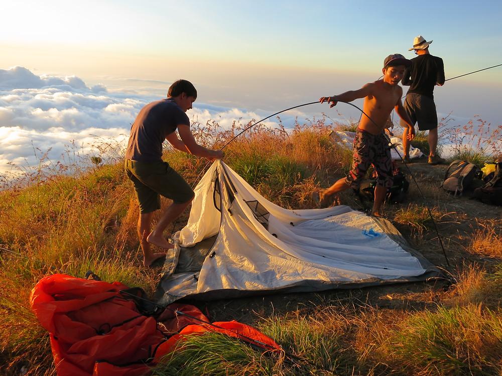 aufbauen des Zeltes ueber den Wolken des Mount Rinjani
