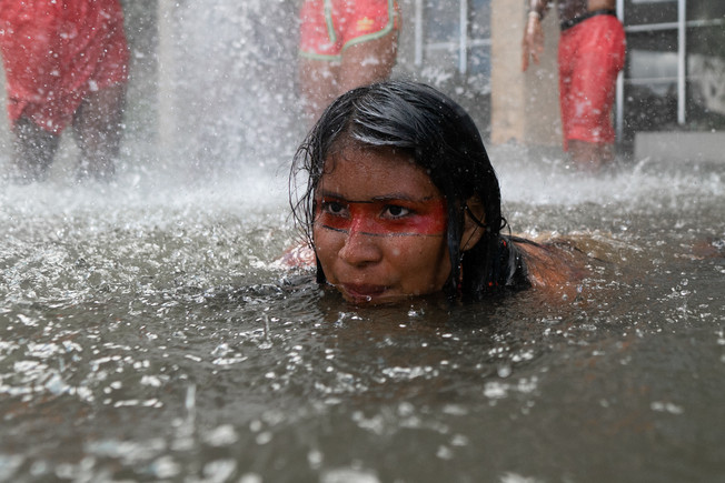 An indigenous woman is seen swimming in the Palace of Justice water mirror as a protest for the demarcation of lands and the maintenance of basic indigenous rights during the XV Acampamento Terra Livre (Free Land Camp), the largest indigenous meeting in the world, in Brasilia, Federal District, Brazil, April 24, 2019. in Brasilia, Federal District, Brazil, April 26, 2019.
