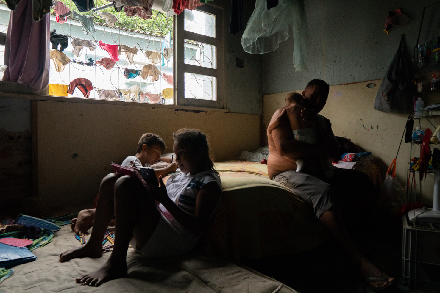 """A fathers holds his baby while his two children study within the informal occupation by Venezuelan immigrants called """"Happy Child"""" at the former headquarters of the Secretariat for Strategic Management and Administration (SEGAD) which houses approximately 450 people in 52 rooms at São Francisco neighborhood due to the lack of financial resources and the overload in the refugee assistance system in Boa Vista, Roraima state, Brazil, June 29, 2020. This building was empty for at least 10 years and has serious structural problems being in danger of collapsing according to the state Civil Defense."""