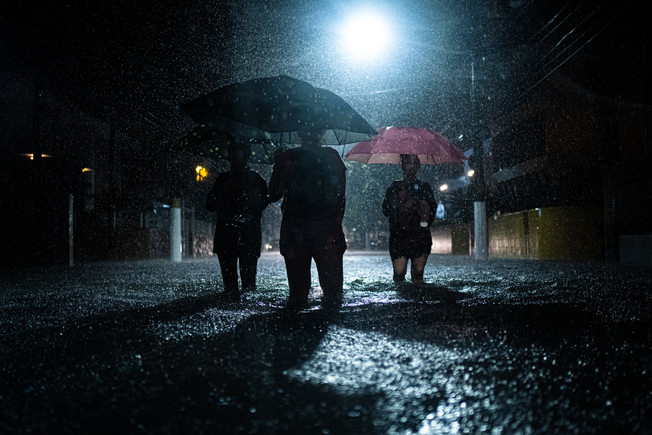Three women walking in the center of the street to cross the flooding point on Rua Azevedo Sodré, near channel 03 in Santos, São Paulo, Brazil, during the night of March 2, 2020.