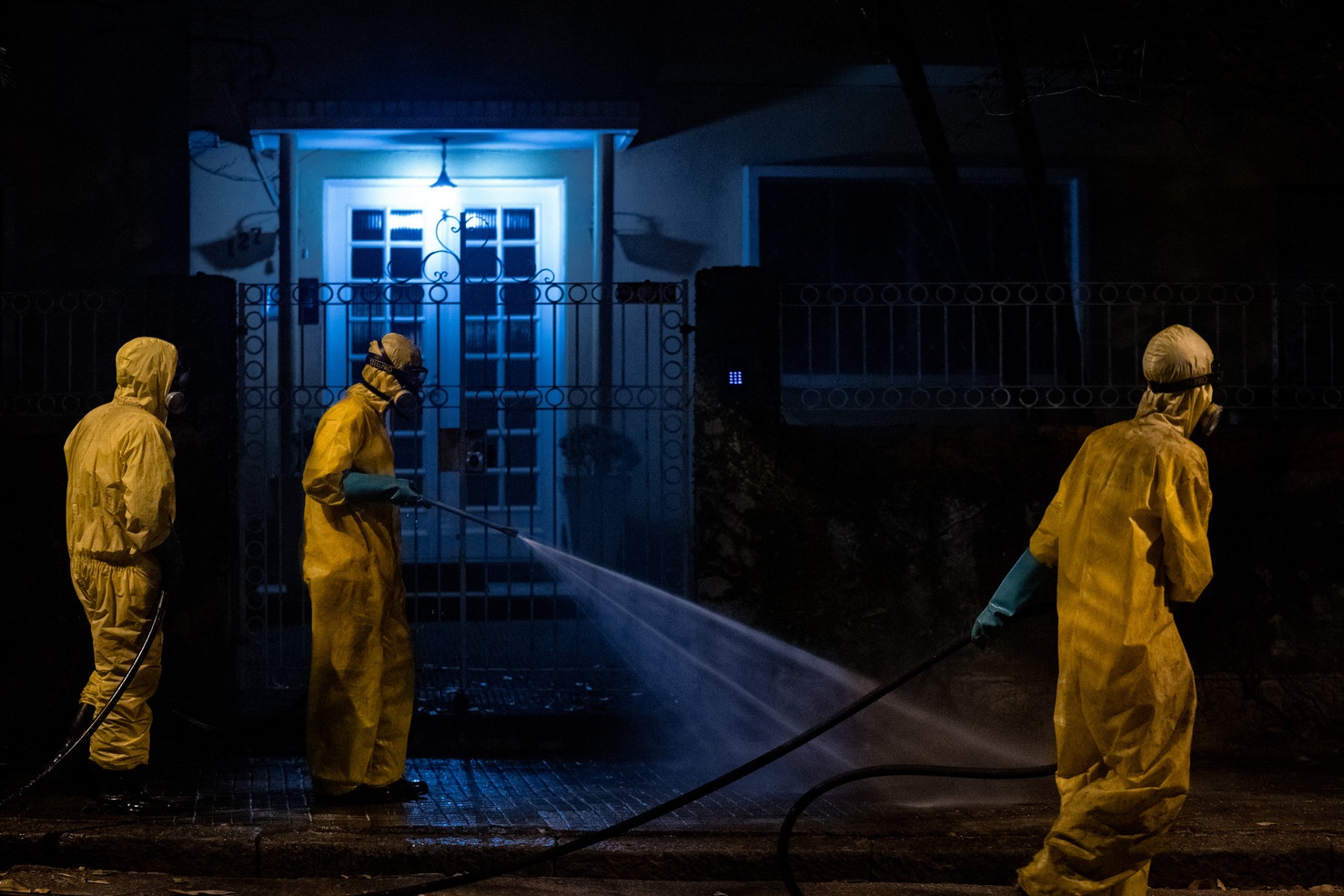 Workers spray desinfecting agent on the sidewalks in Boqueirão neighborhood as a way to combat coronavirus (COVID-19) transmission during the night in Santos, Brazil, April 25, 2020.